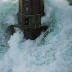 """La Jument lighthouse off the island of Ushant, Brittany, France, photographed by Jean Guichard in 1989. Much discussion of Photoshopping has ensued about this, but it's real. Click through for many photos and the story, plus search his site (http://www.jean-guichard.com/photographs ) for """"jument"""" for many more. Amazing animation here: http://www.alphapix.com/animvague.shtml#jument"""