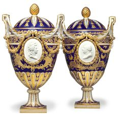 A PAIR OF SEVRES PORCELAIN BLEU NOUVEAU TWO-HANDLED VASES AND COVERS  CIRCA 1774, BLUE INTERLACED L'S MARK, BLUE GILDERS MARK FOR LE GUAY  Each vase egg-shaped, the slightly domed cover with gilt pinecone finial centering alternate radiating single acanthus leaves or pendent bellflowers enriched in gilt on a dark blue ground, the body centering a biscuit portrait medallion of either Marie-Antoinette or Louis XV within a gilt harebell medallion applied to the dark blue ground