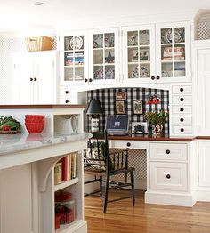 Fuse Flair and Function.    Built-in storage around this kitchen desk provides space for hanging files, office supplies, and electronics. Wall cabinets with glass panels lighten the look of the area and display collectibles. Fabric-covered corkboard adds function and style to the office area.