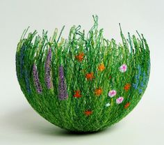 Tiny decorative garden bowl. Made by machine embroidering flowers and grasses in layers onto fabric that can be dissolved, which is molded into a shape before it is removed. By Anne Honeyman, chocolatefrog on Etsy.