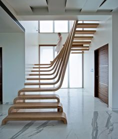 Waves of wood form the staircase inside this Mumbai apartment.