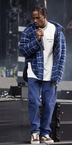 Travis Scott Performs Wearing Balenciaga Jacket, Travis Scott T-Shirt, Palace Pants And JJJJound X Vans Sneakers