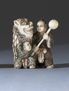 """POLYCHROME IVORY NETSUKE Depicting two figures: one with a shishi mask and one with a banner pole. Signed. Height 2.25"""" (5.5 cm)."""