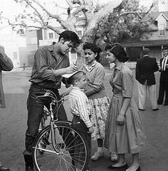 Elvis Presley signs autographs on a kid's head.