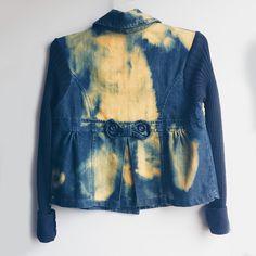 Casaco jeans azul escuro, com manga longa de lã preta e descoloração irregular em amarelo. Fechamento com botões de acrílico. Nas costas, laço e detalhe de movimento.