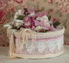 This is a beautiful heavy paper mache large round trinket or hat box that has been covered with a beautiful rose moire fabric. The Bottom edge and top has been covered in an ivory lace. Venetian lace has then been applied over the top. It has been heavily decorated with satin and sheer wired ribbon along with silk roses, cording, fringe and pearl beads. The inside of the box has been lined in an ivory moire and finished with gimp.