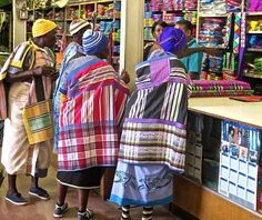 a group of Venda women arrived in the trading store in their characteristic brightly striped wraps. Their blouses were made of printed shwe-shwe indigo cotton. The women tie a bright, stripy cotton wrap over one shoulder. The wraps are embellished with ribbon and braids to make the striped design more complex