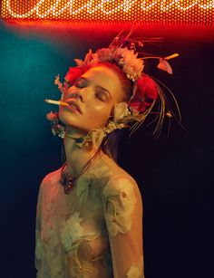 Posing with a cigarette, Sasha Luss models flower crown and floral embellished dress