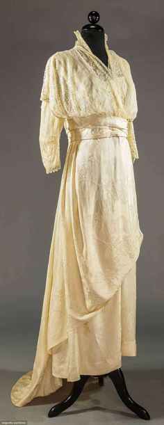 TRAINED CHARMEUSE EVENING GOWN, c. 1912 Cream silk charmeuse w/ vine & blossom pattern, empire bodice w/ silk lace & sequin overlay