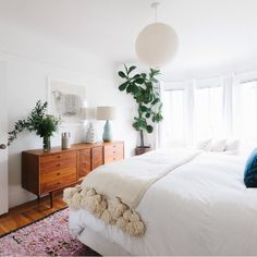 A soft rug, light colours and a stunning light fitting to transform a bedroom into your perfect haven.
