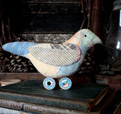 Here we have a sweet little folk art bird make-do that is stuffed firmly. He has a gusset tummy, so he is nice and plump. There may be little imperfections such as tiny holes and tears in this bird as it was made with a old worn quilt top. He is lightly stained to make him look as if he has come from days of old. His wings are made separately and hand stitched in place. He is perched on top of two vintage wooden spools and measures 4 tall by 7 1/2 long. He has a black floss french kn...