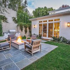 Rectangular Concrete Fire Pit Surrounded by Gray Outdoor Chairs