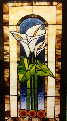 "The first calla lillies that I did.  It's all Kokomo glass, with hand blown rondels. Framed in walnut, this window is 28"" x 40""."