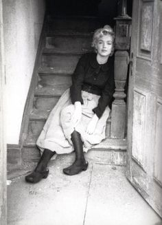 Milton GREENE :: M. Monroe Seated on a Wooden Staircase Wearing a Peasant Skirt