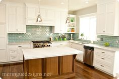 blue glass subway tile backsplash. Brown wood island and white cabinets