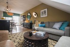 Big living room furnished with a round wooden sidetable from India, It's about RoMi Hollywood standing lamp and hanging lights, chandelier made from bambus ply and oriental mirror. Walls are painted in olive and blue-grey colors. #interior #design #homedecor #olive #blue #livingroom #india #wooden #sidetable #sofa #handmade #carpet