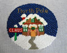 """Diane's Taking Time Out To Needlepoint:  North Pole ornament by Silver Needle. Love the Rainbow Gallery Alabaster for the French knots on the roof, chimney, and on top of the """"Claus"""" sign. Alabaster over the door and windows,  used Caron """"Snow"""" in a nubuko stitch for the snow on the ground."""