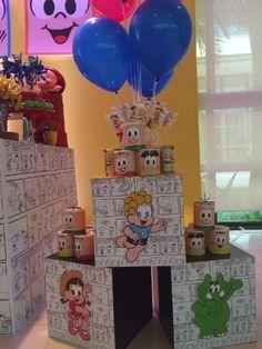 Cubos adesivados com quadrinhos serviram como apoio para latinhas personalizadas com batatas, pirulitos de marshmallows, além de bolinhas de sabão. Ao centro, balões de gás hélio com as cores do tema da festa, da Milla Arteira (www.facebook.com/MillaArteira)