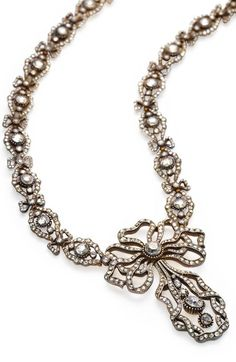 Cartier - A Belle Epoque diamond necklace, circa 1906. Designed as a series of openwork oval-shaped rose-cut diamond links with rose-cut bow spacers and suspending a rose-cut pendant of elaborate bow motif accentuated by a central old European-cut diamond and further graduated old European-cut diamond articulate four-stone line; signed Cartier Paris, numbered; mounted in silver topped gold. #Cartier #BelleÉpoque #necklace