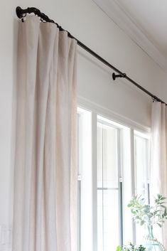 How to make no sew drop cloth curtains to fit any window size. This is a cheap and easy alternative to expensive drapes and window treatments.
