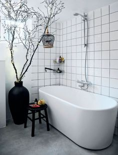 Black stool and potted branches with string lights add drama and elegance to an otherwise pure white bathroom.