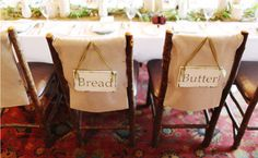 """We love the idea of hanging cute signs on the back of the bride's and groom's chairs even more when the words mean something special. This couple chose """"bread"""" and """"butter,"""" but you could pick """"peas"""" and """"carrots""""; """"horse"""" and """"carriage""""; """"tea"""" and """"crumpets""""; """"salt"""" and """"pepper""""; or """"wink"""" and """"smile."""""""