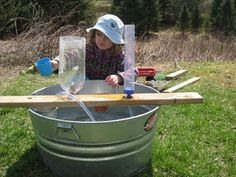Drill some holes in a plank and add a cut-off soda bottle, some clear tubing, anything you can pour water into.  Place board over a tub and play!