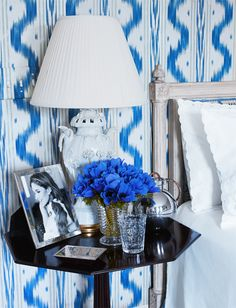 aerin lauder's southampton bedroom that is still decorated as estée had it with wall upholstered in blue-and-white pierre frey toile de nantes print.
