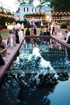 outdoor cocktail party+globe lights over pool, white house and green lawn