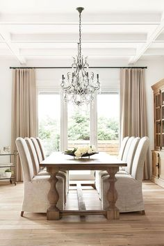 I like how simple this dining room is paired with the fancy chandelier. I'm not sure how I feel about the chairs with the long cover over them - but with that table it gives good balance since the table is rustic.  Dining room