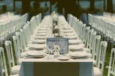 imperial table on the grass, white elegant chairs and natural centrepiece!