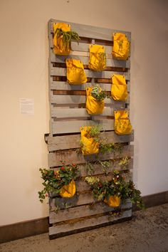 Idea from the May Flea Off Market. 2 Pallets painted, stacked on top of each other, and fastened to a wall. Bags are fastened to the pallets for plants.        The bottom of the stack is filled with dirt, etc as well.       Easy to do and looks really cool.