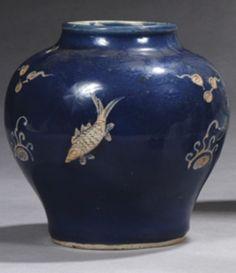 Époque MING (1368-1644),  Petite jarre balustre en porcelaine émaillée bleu à décor en réserve et en léger relief de carpes nageant parmi des perles sacrées. Hauteur : 15 cm