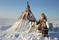 §§§ . Oksana, Nenets woman carrying an arctic hare outside her family's winter tent on the tundra. Gydan, W. Siberia, Russia.