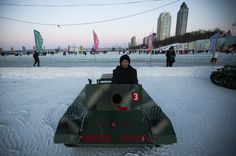 According to a commenter, this tank says: Drive this tank, Recapture the Diaoyu Islands! 开着坦克跑,收复钓鱼岛!Harbin International Ice and Snow Festival 2013 - The Big Picture