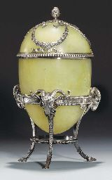 A silver-mounted bowenite bonbonnière shaped as an egg by Fabergé, workmaster Julius Rappoport, St. Petersburg, circa 1890. The thinly carved bowenite body divided in two halves, the upper half mounted with silver laurel-leaf ribbon-tied swags above a reeded rim, surmounted with a bud finial, emanating from acanthus leaves, on a silver tripod stand with three hoof feet, each surmounted by a ram's head.
