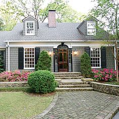 groups of three boxwoods with larger boxwoods on either side, gabled overhang at door : Charming Cottage Curb Appeal Makeover - Southern Living