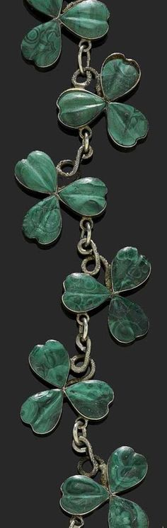 MALACHITE AND SILVER NECKLACE, SCOTLAND, CIRCA 1880. Very decorative necklace of shamrock motifs , joined by engraved tendrils. The clovers are paved with finely cut malachites.