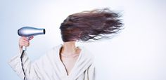 Woman blow-drying wavy hair