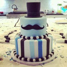 "Mustache Cake-top hat as top layer and solid blue with stache as bottom layer.  ""Happy Birthday, Brianna"" written on cake board."