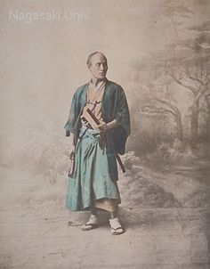 "This is a studio photograph of a samurai wearing a haori jacket (with a family crest) and hakama pants. ""Japan 1881"" is penciled in. The backdrop suggests that it is from the Stillfried album. The samurai may be holding an imitation wooden sword. He also has a fan in his hand. On the back of the photograph is a photograph of Alexandria by Felix Bonfils."