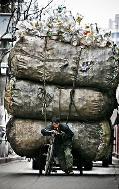 Shanghai Zhongshan Road West, a scavengers pulling a trailer full of scrap, looked tired, heavy footsteps, China, 2003
