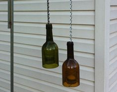 Upcycled wine bottles get a second life as quirky candle holder lanterns. Each bottle is flame cut and edges are beveled. Then each bottle rim is sanded in a three-part process to ensure smoothness. Clear glass votive holder is held in place by spiral wire and can be raised and lowered on chain for lighting or cleaning. No two are exactly alike (though if youd like a matched pair, I will make a set). Includes tea light candle. Available colors are green, amber, and slightly tinted clear…