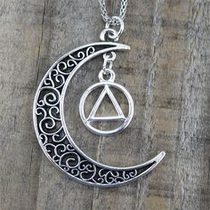 """Alcoholics Anonymous charm surrounded by a delicate antiqued silver filagree moon. The moon is 38mm x 35mm. The moon hangs from a 24"""" stainless steel rope chain with clasp. Our higher power is like th"""
