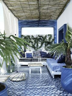 A terrace beautifully co-ordinated blue and white outdoor room on a terrace.