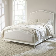 Pairing carved wood molding and neutral upholstery, this elegant bed looks lovely topped with a resort-worthy duvet or classic quilt.