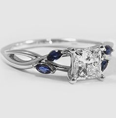 Wispy vines of precious metal entwine toward lustrous marquise sapphire buds