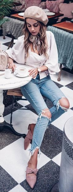 #spring #outfits woman wearing white long-sleeved blouse with distressed blue denim jeans sitting on chair holding teacup. Pic by @speak__fashion