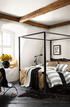 Ralph Lauren Home's four-post canopy bed with head and footboards in woven seagrass is dressed in casual, black and white striped linen bedding.