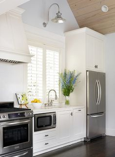Gorgeous white kitchen with dark hardwood floors and plantation shutters. LOVE THE COLORS AND PLANTATION SHUTTERS.